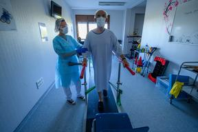 A physiotherapist helps a patient in rehabilitation as he recovers from Covid-19, at a hospital in eastern France, on 14 April, 2020.