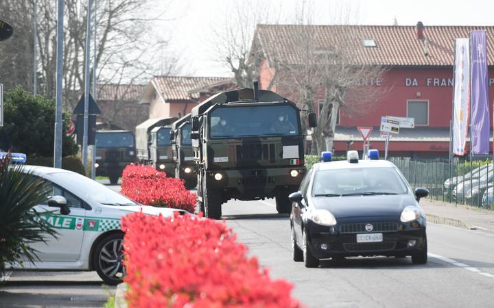 This picture shows a military convoy outside the church of San Giuseppe in Seriate, Italy on March 28, 2020, as coffins of people deceased from the COVID-19 novel coronavirus are carried to be blessed inside the church.