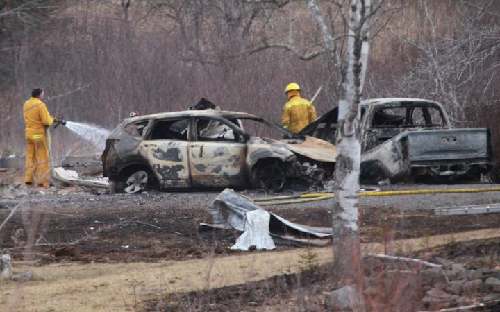 A Wentworth volunteer firefighter douses hotspots near destroyed vehicles linked to Sunday's deadly shooting rampage on April 20, 2020 in Wentworth Centre, Nova Scotia, Canada.