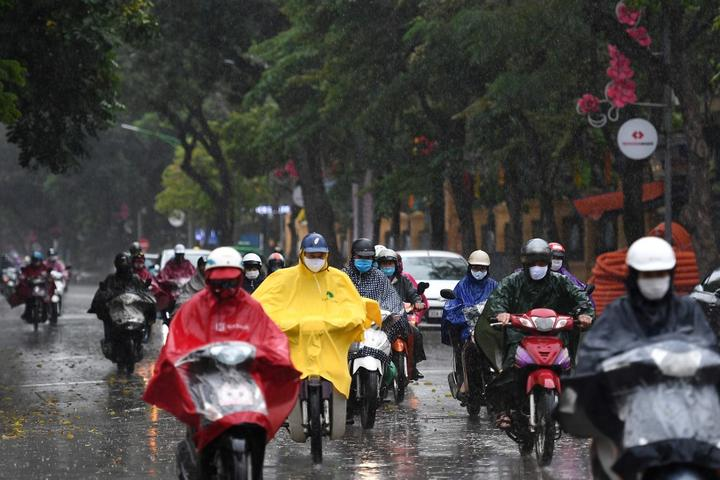 Motorists wearing face masks ride amid a downpour in Hanoi as Vietnam eased its nationwide social isolation effort to prevent the spread of the COVID-19.