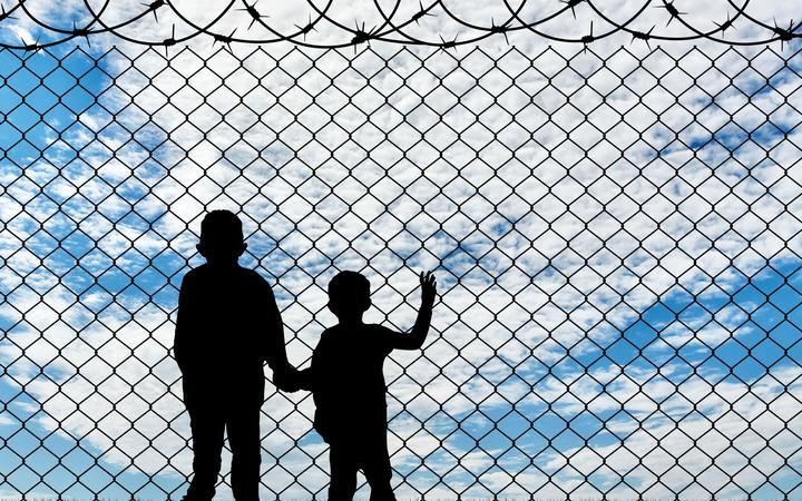 Refugee children concept. Silhouette of two children of refugees near the border fence of barbed wire