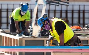 Masked construction workers are pictured at a building site on the first day of the easing of restrictions in Wellington on April 28, 2020, following the COVID-19 coronavirus outbreak. -