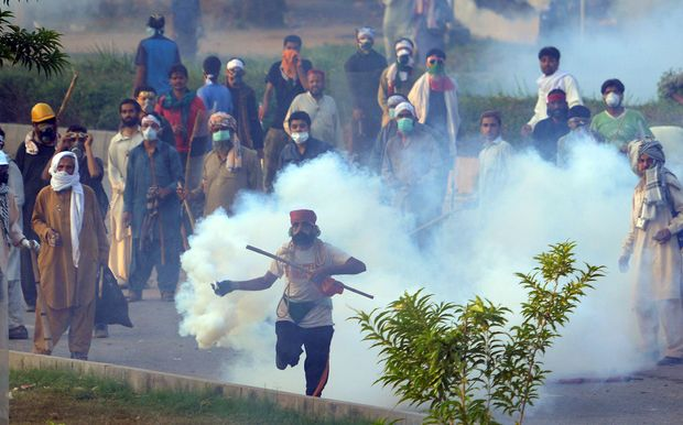 A Pakistani supporter of the Canadian cleric Tahir ul Qadri returns a tear gas shell towards police during clashes with security forces.