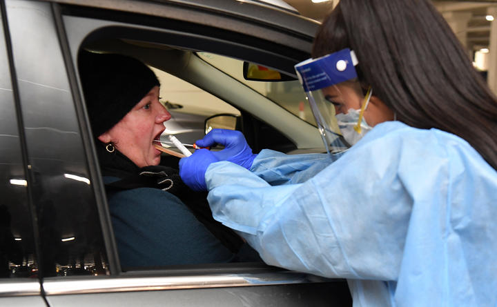 Medical staff perform a test for the COVID-19 coronavirus on a driver at a drive-through testing site in a Melbourne carpark on May 1, 2020.