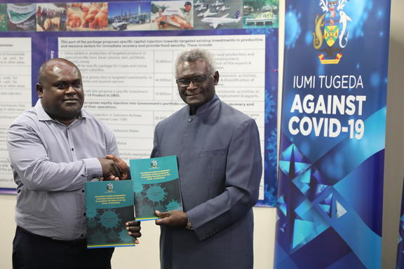 Prime Minister Manasseh Sogavare (right) hands the Economic Stimulus Package document over to the Minister of Finance and Treasury, Harry Kuma.