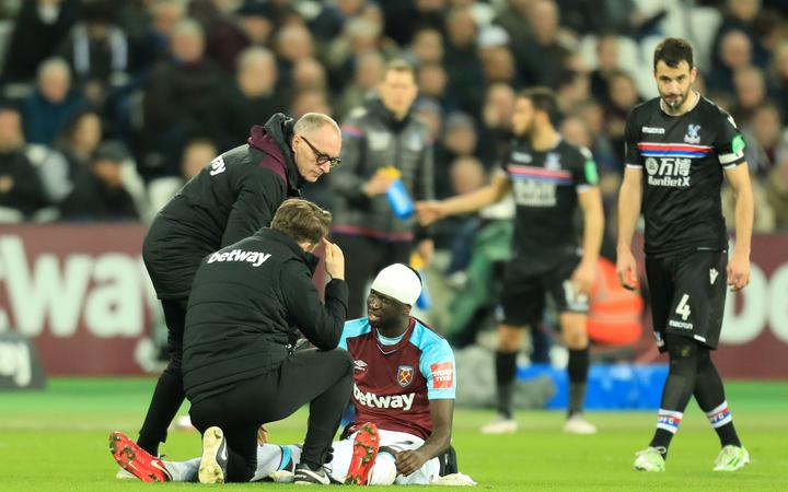 Cheikhou Kouyate of West Ham United is checked by the doctor after having his head bandaged