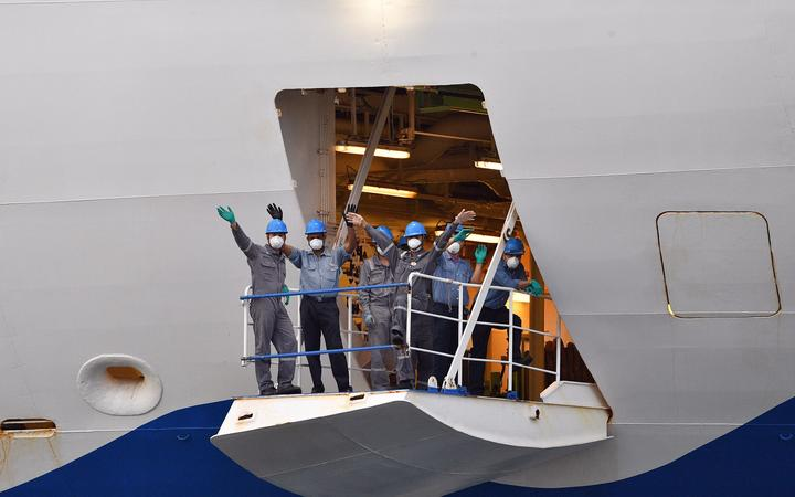 Crew members from the cruise ship Ruby Princess wave as they depart from Port Kembla, some 80 kilometres south of Sydney, on April 23, 2020, after a few hundred virus-free crew members disembarked to begin the process of repatriation to their home countries. -
