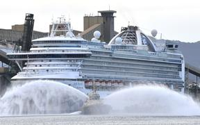 A tug boat gives a water salute as cruise liner Ruby Princess prepares to leave Port Kembla, some 80 kilometres south of Sydney on April 23, 2020.