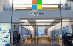 People walk past a Microsoft store entrance with the company's logo on top in midtown Manhattan at the 5th avenue in New York City, US.