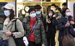 Mask-clad commuters get off a train at a Mass Rapid Transit (MRT) stop in Taipei following the Lunar New Year holidays on January 30, 2020.