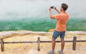New Zealand travel tourist taking phone picture of famous attraction Champagne pool, Waiotapu.  Rotorua,
