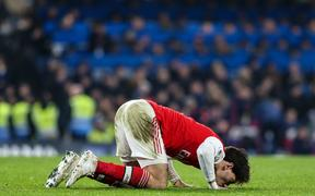 Hector Bellerin of Arsenal kisses the pitch.