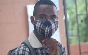 A Kopkop college student wearing a mask.