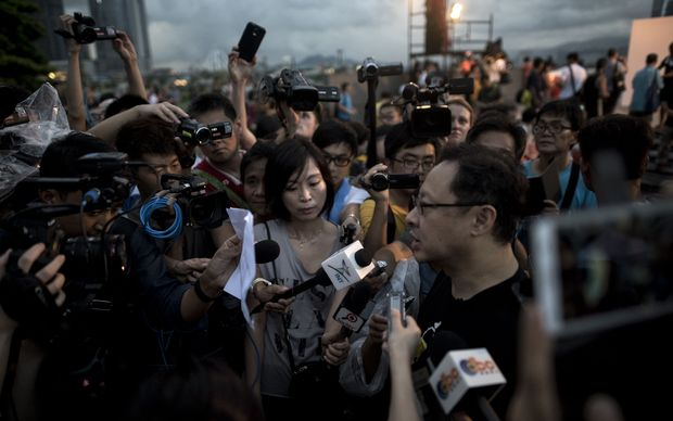Benny Tai (right), co-founder of the Occupy Central movement, talks to the media at a rally near the Hong Kong government complex.