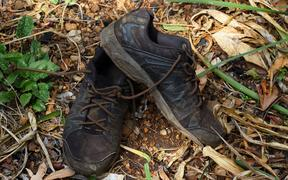 89175150 - pair of dirty old black shoes abandoned outdoors in landscape format