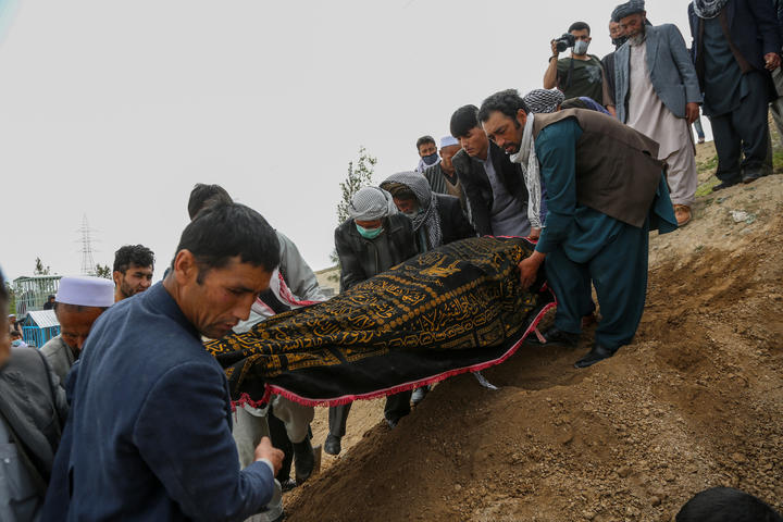 Mourners burying a loved one, following a suicide attack in a maternity hospital in Kabul.
