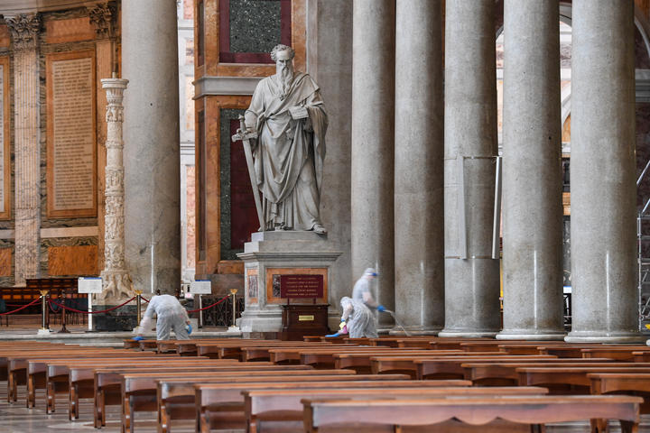 Men clean the floor and surfaces of the churchyard of the Basilica of Saint Paul Outside The Walls in Rome, on 16 May.