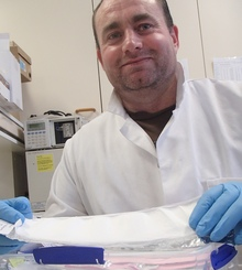 Pharmacist Greg Walker holds experimental nano-fibre wound dressings, that have been created using electro-spinning and contain polyphenols produced from wine waste.