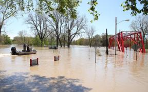 MIDLAND, MICHIGAN - MAY 20: Residents in boats inspect the floodwaters flowing from the Tittabawassee River into the lower part of downtown on May 20, 2020 in Midland, Michigan.
