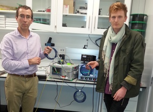 A photo of Neil Broderick and Patrick Bowen with the equipment that measures light in the optic fibres