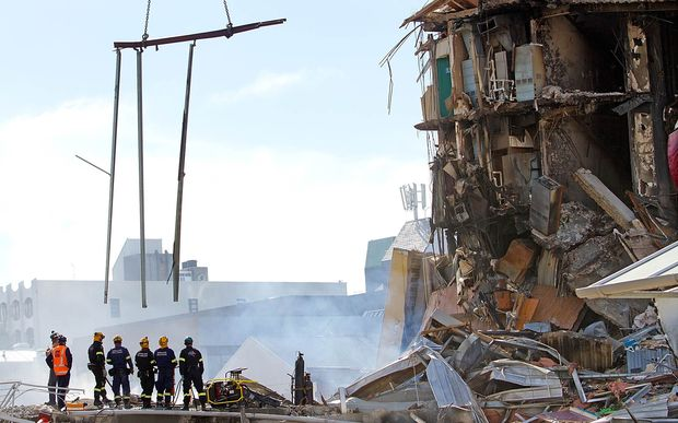 Rescuers stand in the smoking ruins of the CTV building two days after the quake in 2011.