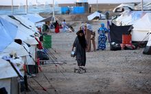 An Iraqi woman who fled violence in the northern city of Tal Afar walks through the Bahrka camp, in the autonomous Kurdish region.