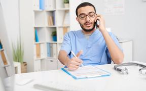 Portrait of young Middle-Eastern doctor wearing glasses sitting at desk in office and speaking by smartphone, filling in patients forms