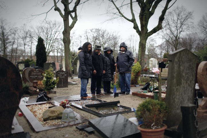 A family of West Papuan refugees grieving at the grave of Seth Jafeth Rumkorem in the Hague.