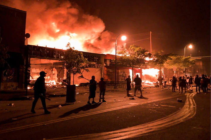 Flames rise from a liquor store and shops near a police station set on fire during a third night of protests in Minneapolis.