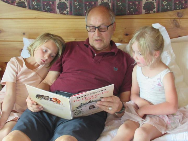 Jack Saprunoff, reading to grandchildren Ivy (left) and Zosia Costello.