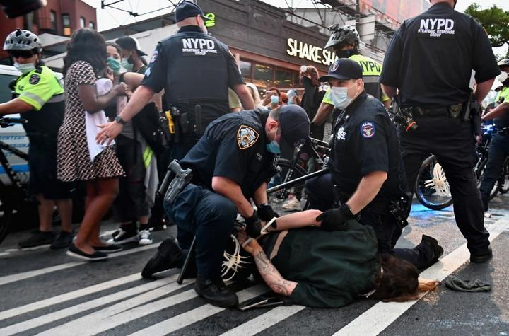 Police officers cuff a protestor during a