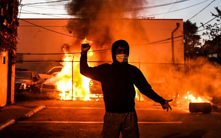 A protestor gestures as cars burn behind him during a demonstration in Minneapolis, Minnesota, on May 29, 2020 over the death of George Floyd, a black man who died after a white policeman kneeled on his neck for several minutes.