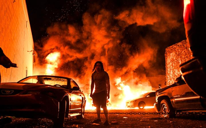 A man tries to toe away a car in a safe zone as the other car catches fire in a local parking garage on May 29, 2020 in Minneapolis, Minnesota, during a protest over the death of George Floyd, an unarmed black man,