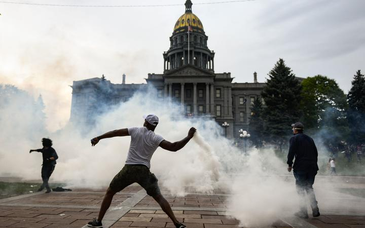 A man throws a tear gas canister back at police officers in front of the Colorado State Capitol as protests against the death of George Floyd continue.