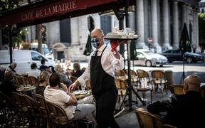 A masked waiter works at the terrace of the Cafe de la Mairie on the Place Saint-Sulpice in Paris on June 2, 2020, as cafes and restaurants reopen in France.