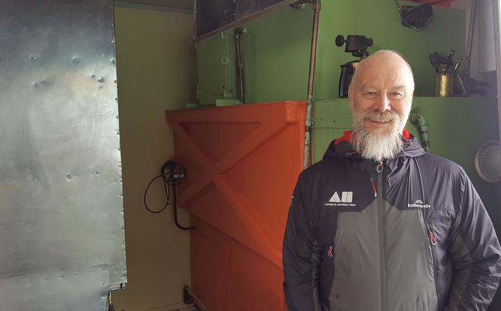 Conservator Al Fastier works for the Antarctic Heritage Trust. He is standing next to one of his favourite artefacts in Hillary Hut, also known as Hut A from the original Scott Base - the water-maker used to melt glacier ice.