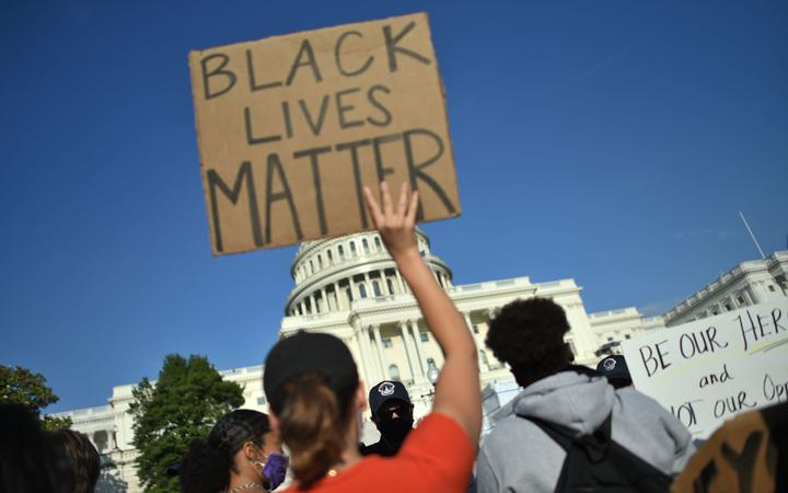 Protesters hold signs as they demonstrate in front of the United States Capitol in Washington DC on 2 June 2020