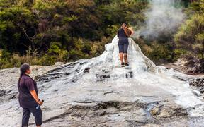 VALLEY OF GEYSERS ROTOROU, NEW ZEALAND - MARCH 24, 2018. The famous geyser of Lady Knox. The girl fills up in a geyser soap mixture to activate the eruption.