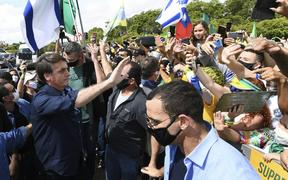 Brazil's President Jair Bolsonaro greets supporters upon arrival at Planalto Palace in Brasilia, on May 24, 2020. Despite positive signs elsewhere, the disease continued its surge in large parts of South America.
