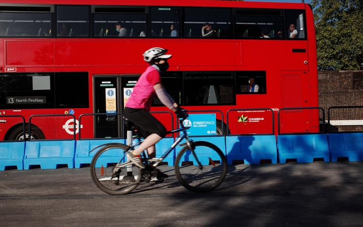 A cyclist rides along a section of the Mayor of London's 'Streetspace' scheme, designed to expand capacity for pedestrians and cyclists on certain roads while social distancing guidelines remain in effect, on Park Lane in London, England, on May 28, 2020.