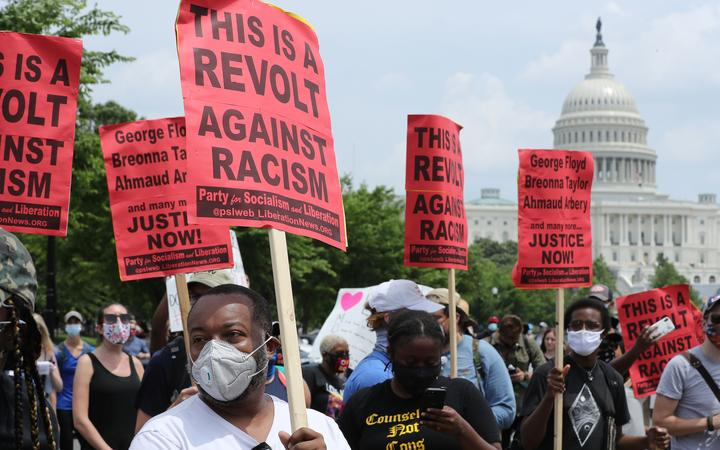 Demonstrators carrying signs gather near the U.S. Capitol during a protest against police brutality and racism on June 6, 2020 in Washington, DC.