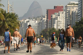 People walk along the edge of Copacabana beach in Rio de Janeiro, Brazil. The country's Covid-19 death toll has surpassed Italy.
