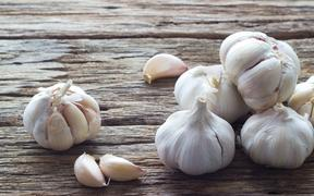 Garlic and garlic cloves on a wooden background.