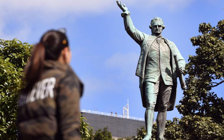 People walk past a statue of Captain James Cook in Sydney's Hyde Park on August 25, 2017,