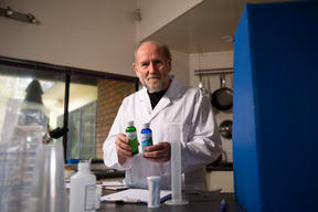 Forensic scientist Dr Ian Calhaem holding sodium chlorite and hydrochloric acid.