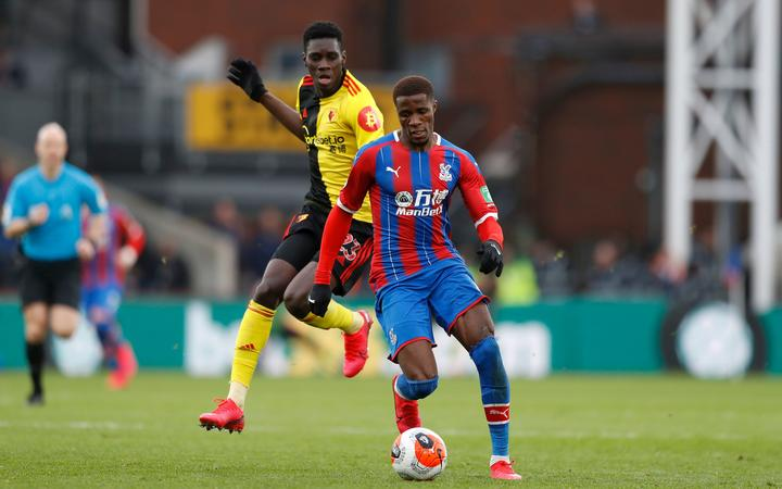 Wilfried Zaha of Crystal Palace runs past Ismaila Sarr of Watford