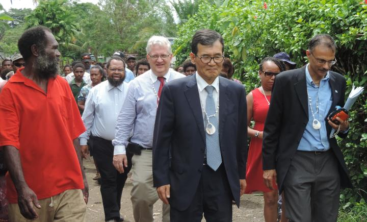 Dr Albert Schram with UN and Korean government officials during a visit to a settlement in Madang.