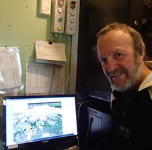 Department of Conservation volcanology advisor Harry Keys sits next to the Eruption Detection System that interprets potential volcanic hazards on Mount Ruapehu and sets off public warnings