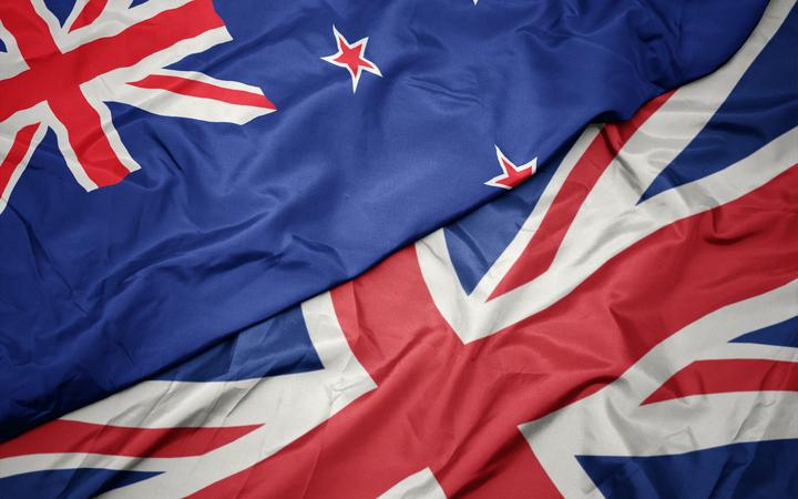 waving colorful flag of great britain and national flag of new zealand. macro