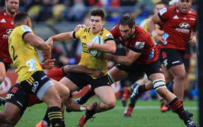 Hurricanes' Jackson Garden-Bachop is tackled by Crusaders Samuel Whitelock.